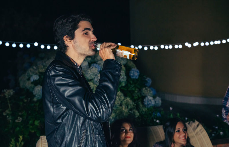 Side View Of Young Man Drinking Beer While Standing At Patio During Night