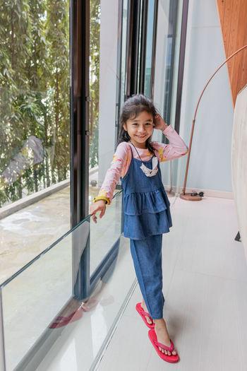 Full length of cute girl standing against wall
