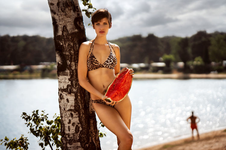 Portrait of model in bikini posing with watermelon at beach