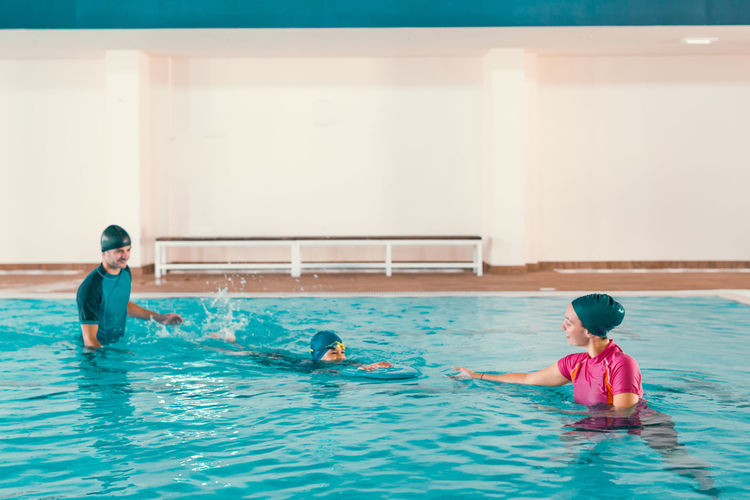 Boy learning to swim in pool with teacher
