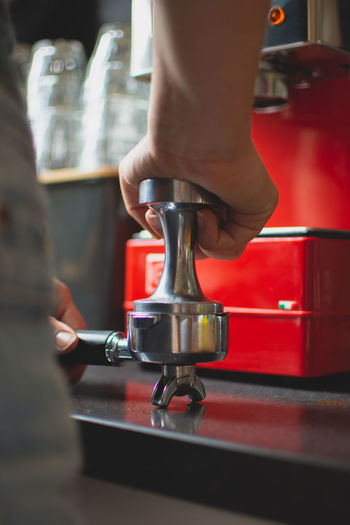 Cropped Image Of Man Pressing Coffee In Portafilter