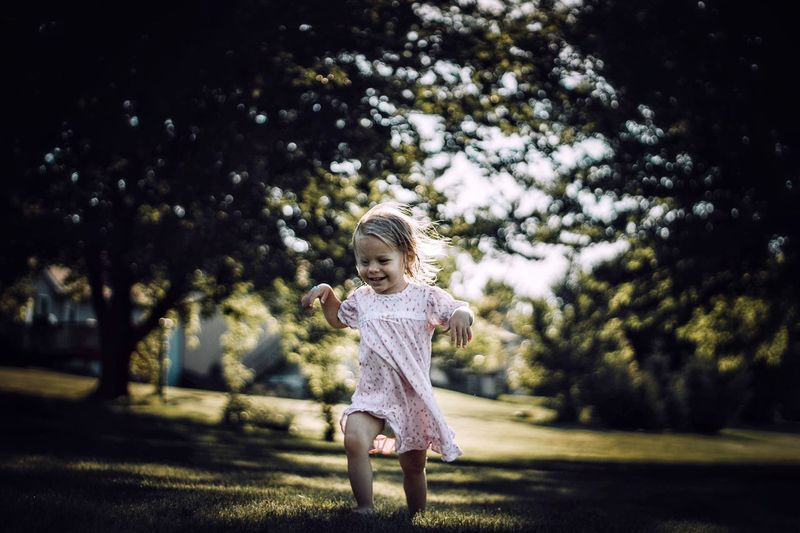 Full length of cheerful baby girl walking on grassy field