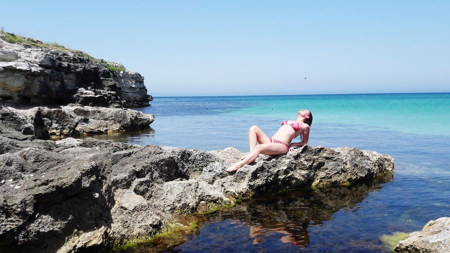 Woman reclining on rock by sea against clear sky