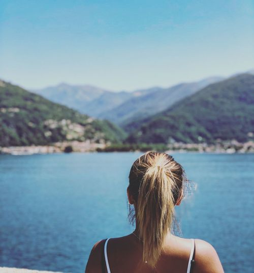 Rear view of woman looking at lake and mountains