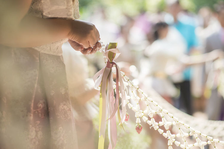 Midsection of woman holding flower decoration during wedding