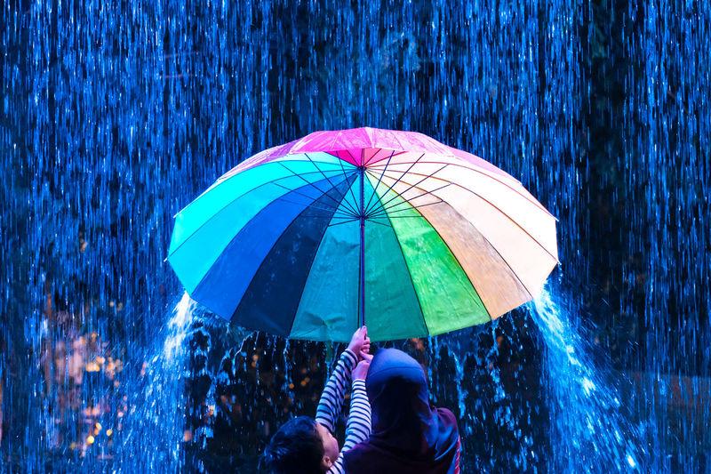 Rear view of children holding umbrella under rain during night