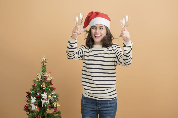 Smiling woman with wineglasses standing by christmas tree against orange background