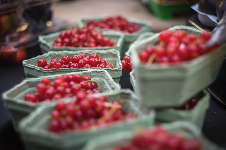 Close-up of red currents in containers at market