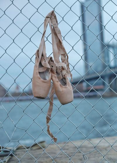 Abandoned ballet shoes hanging on chainlink fence