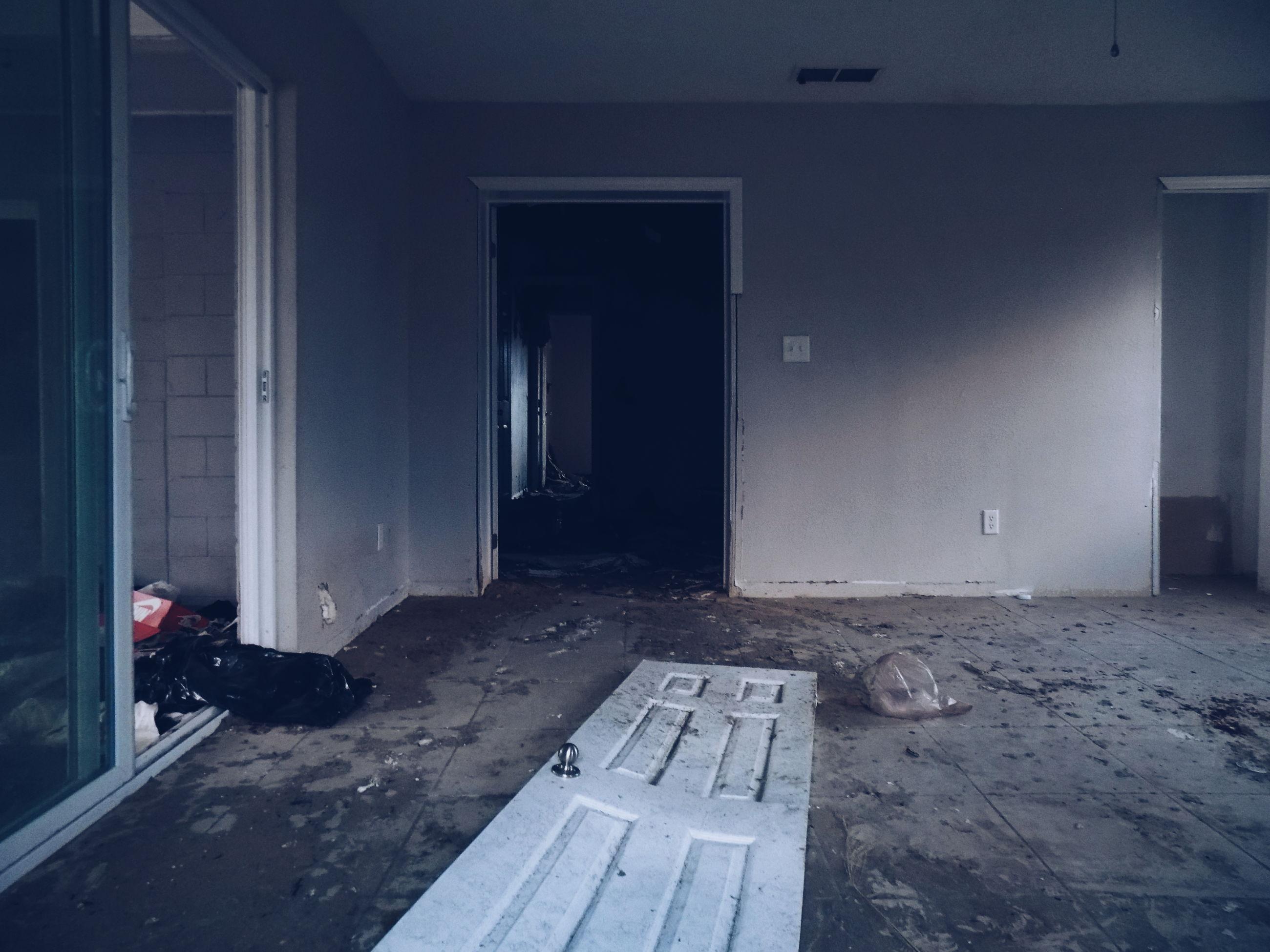 MAN WITH OPEN DOOR ON BUILDING