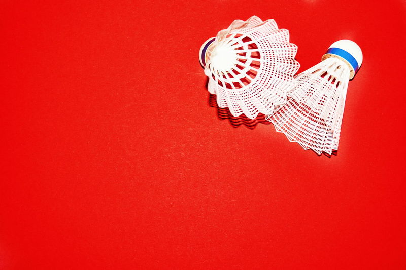 Close Up Of Shuttlecock On Red Background
