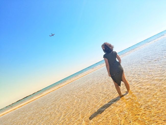 girl at the sea looks at airplane Airplane Beach Beauty In Nature Casual Clothing Clear Sky Day Flying Full Length Land Leisure Activity Lifestyles Mid-air Nature One Person Outdoors Real People Sand Sea Sky Sunlight Women