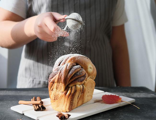 Teenager girl powdering pull apart cinnamon swirl bread with sugar. traditional sweet loaf