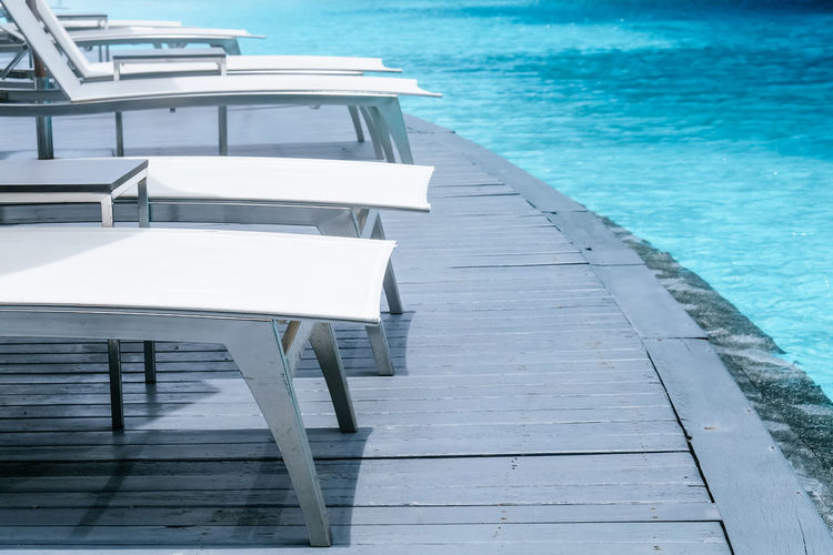 High angle view of empty chairs by swimming pool
