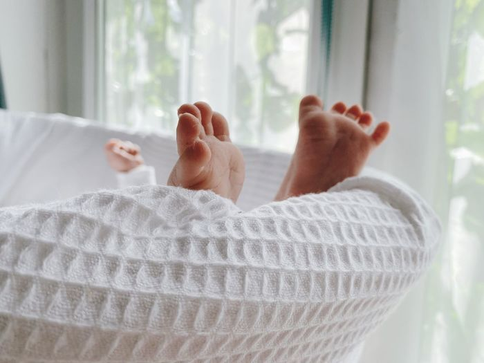 Low section of person relaxing on bed
