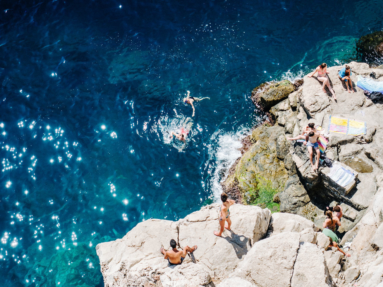 High angle view of people on rock over sea