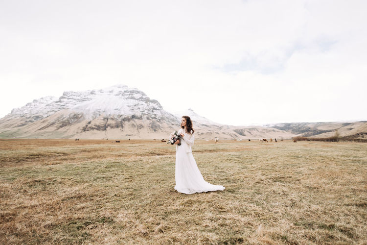 Full length of woman standing on field against mountain