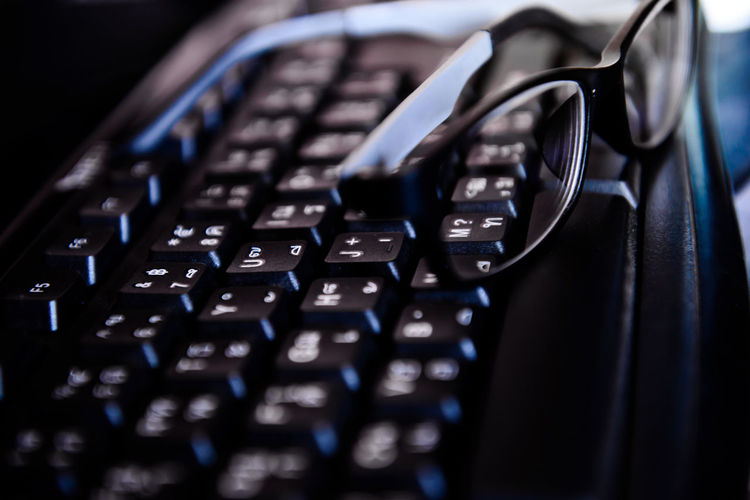 Close-Up Of Computer Keyboard And Eyeglasses