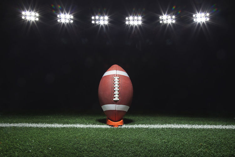 Rugby Ball On Field Against Illuminated Floodlights At Night
