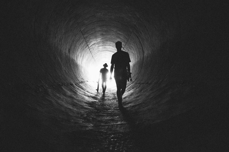 Rear view of silhouette men walking in tunnel