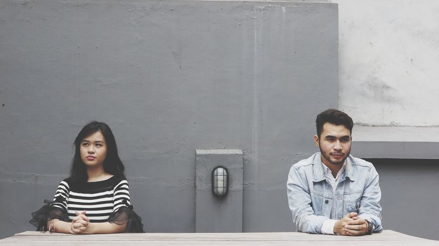 Thoughtful couple sitting against wall