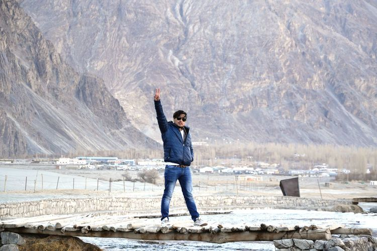Full length of man standing on mountain during winter