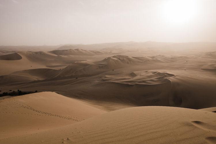 Scenic view of huacachina desert against sky.