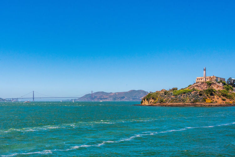 Alcatraz Sea Water Architecture Built Structure Blue Sky Land Scenics - Nature Clear Sky Copy Space Building Exterior No People Nature Beauty In Nature Mountain Beach Travel Destinations Day Building Outdoors Guidance Bay Sailboat