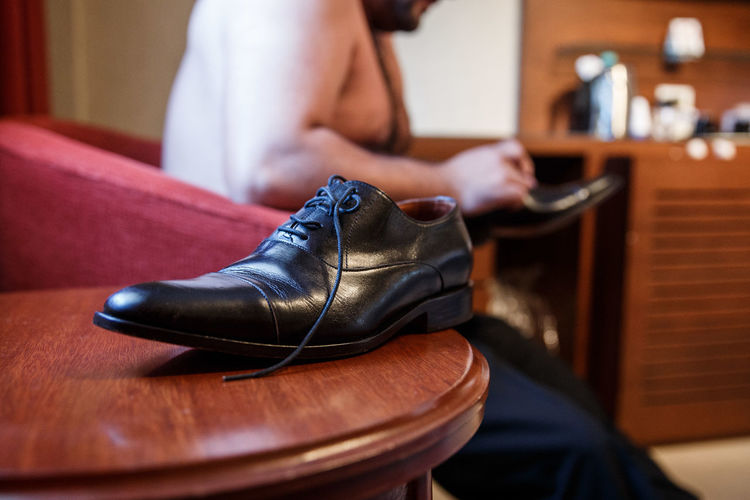 Close-up of shoe on table against shirtless man sitting on sofa