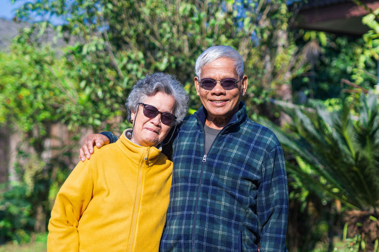 Portrait of elderly couple wearing sunglasses standing and smiling in garden.