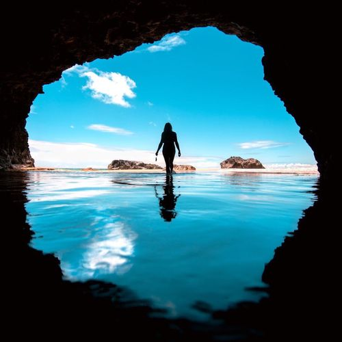 Silhouette Woman Standing With Reflection In Cave Against Sky