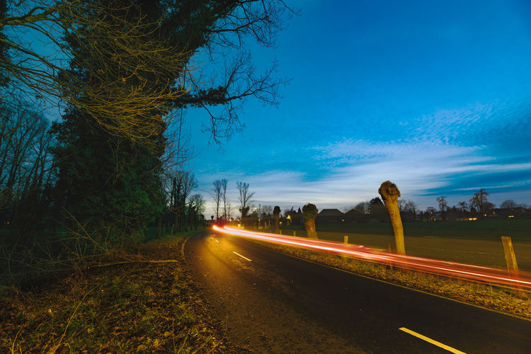Country Roads at Blue Hour Nikon D810 Road Transportation Tree Plant Direction The Way Forward Sky Nature No People Diminishing Perspective Illuminated Street Light Trail Motion Speed Long Exposure Tranquility Blue Symbol Outdoors