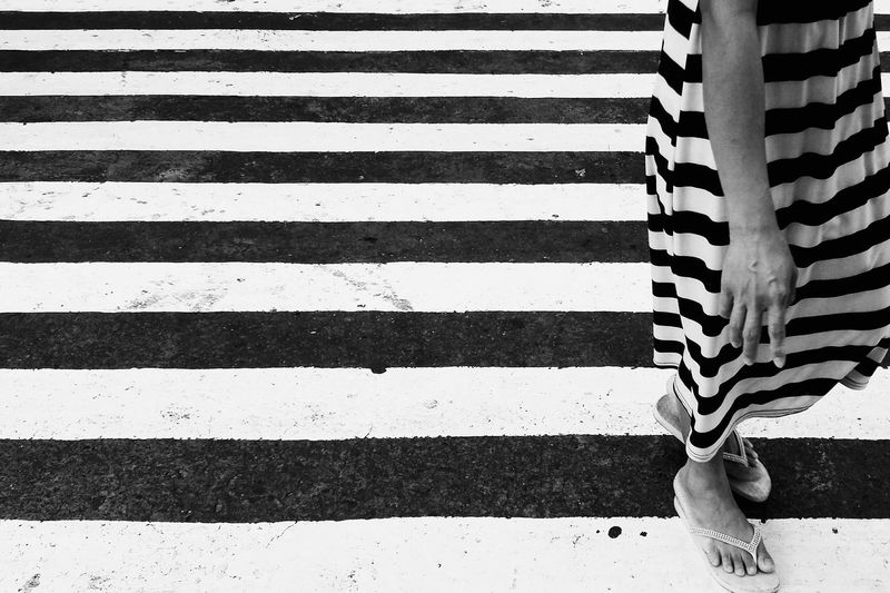 Low section of woman standing on zebra crossing