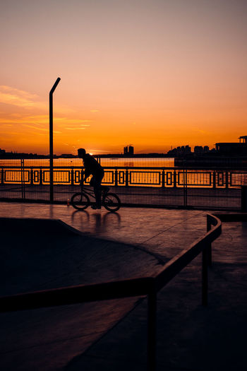 Silhouette man riding bicycle on bridge against sky during sunset