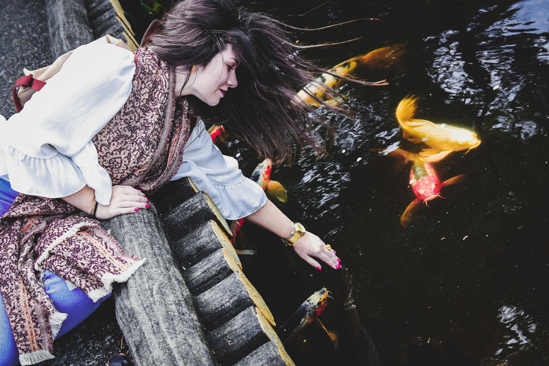 Beautiful girl next to koi fishes