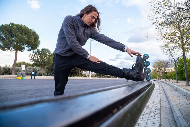 Full length of man skateboarding on road against sky