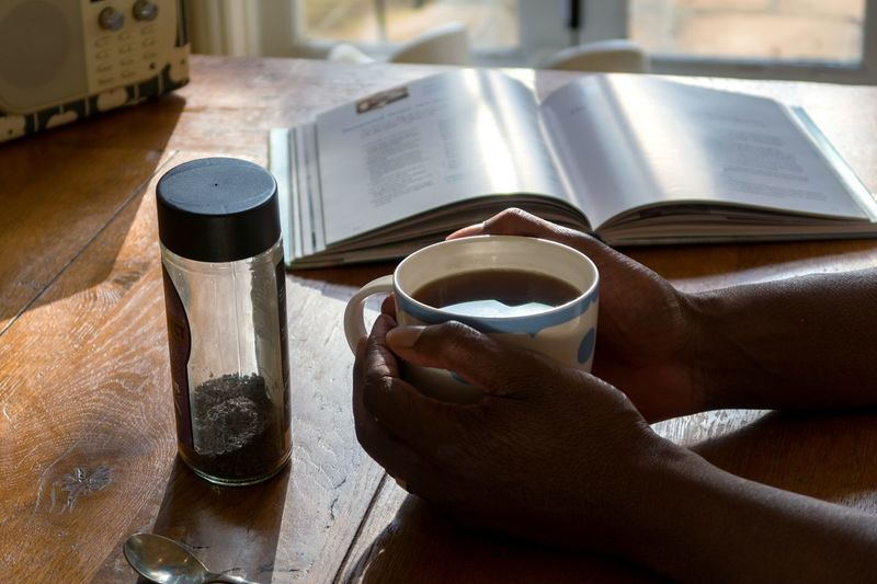 Coffee Human Hand Table Kitchen Wooden Table One Person Drink Indoors  Cookery Book Book Cooking Book Radio Backlit Home Coffee Jar London England African American Afro Caribbean Person Of Color Breathing Space Be. Ready. See The Light