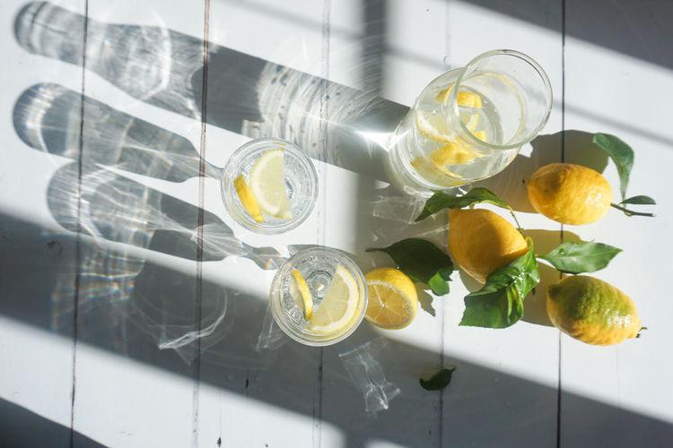 lemonade Water Drink Directly Above White Background Copy Space Lemon Lemons Citrus Fruit Citrus  Yellow White Background Lemonade Cold Drink Vitamin C Fruit Citrus Fruit Yellow Lemon Close-up Food And Drink Beverage Halved Served Fruit Juice