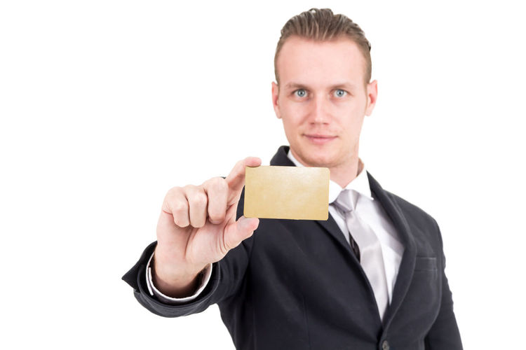 Portrait Of Businessman Holding Card Against White Background