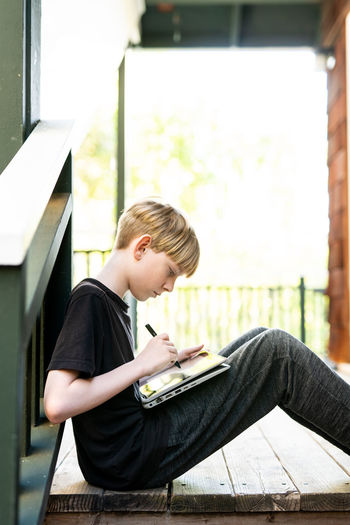 Side view of boy sitting outdoors