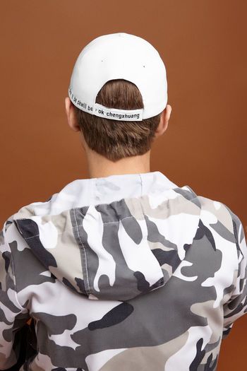 Rear view of boy standing against white background