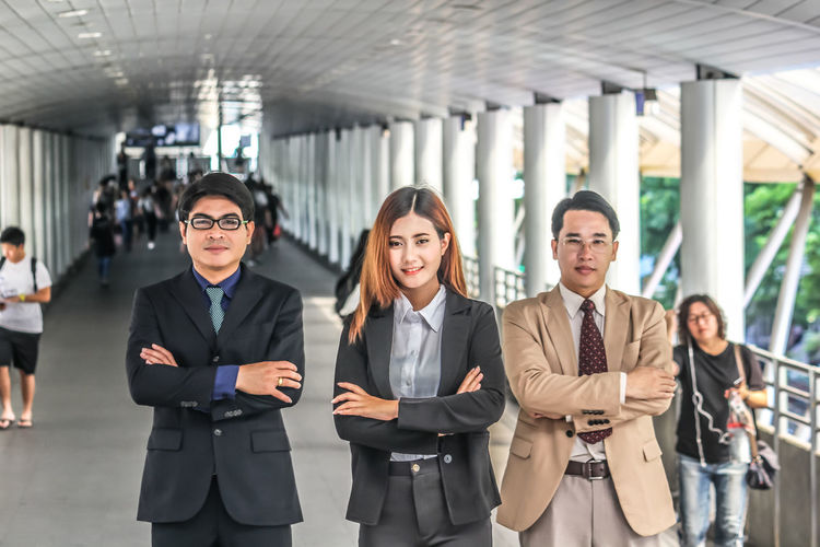 Portrait of colleagues with arms crossed standing on bridge in city