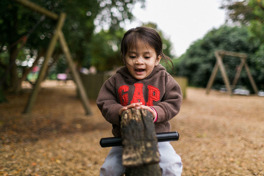 A Girl Playing at the park near Windermere Fun Casual Clothing Childhood Front View Happiness Kids Funny Costumes Leisure Activity Lifestyles One Person Outdoors Playarea Playing Portrait Real People Tree