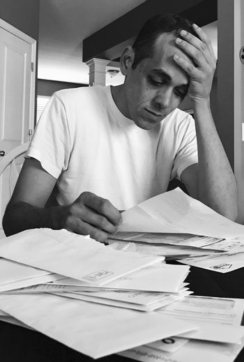 Stressed Man With Paperwork At Home