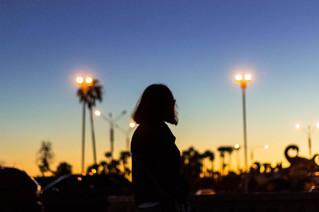 Silhouette woman standing on street against sky during sunset