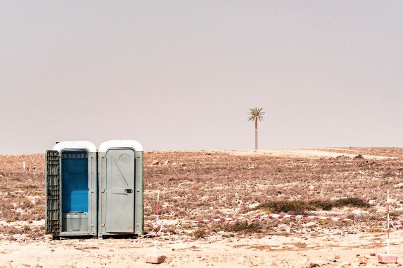 Portable toilet in dessert against clear sky
