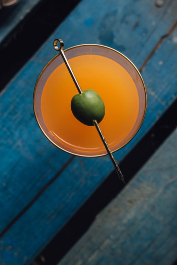 Carrot orange drink with green olive on cocktail pick against blue wood