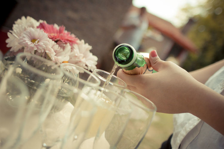 Cropped Hand Of Woman Pouring Champagne In Flute On Table At Wedding