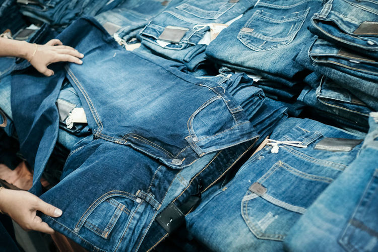 Cropped hands of person buying jeans at store
