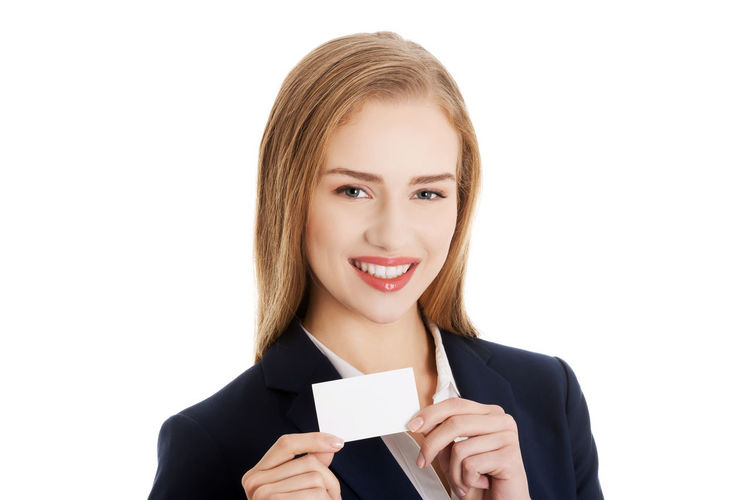 Portrait Of Smiling Businesswoman Holding Card Against White Background